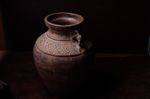 Earthenware jug standing on dark room